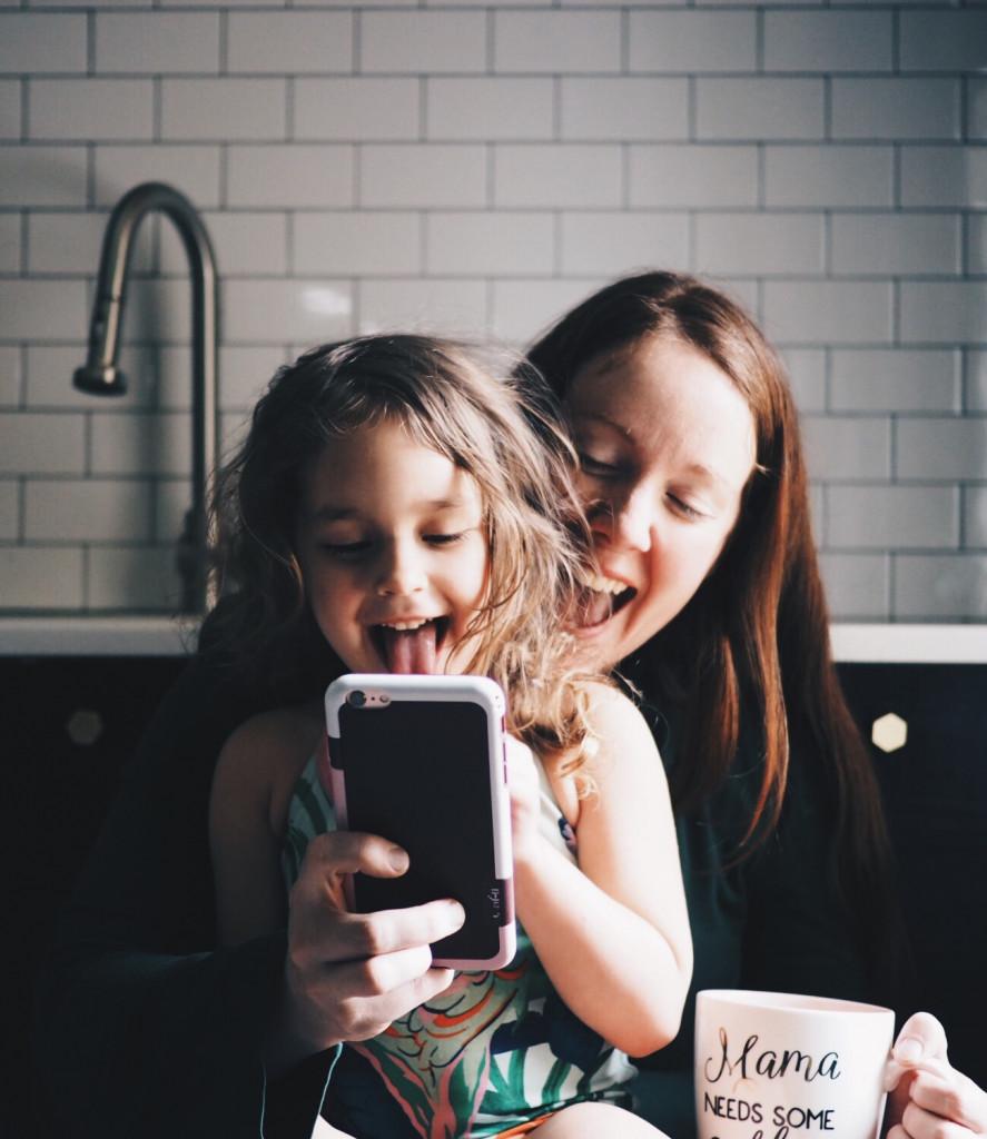 Femme et enfant rigolent devant un téléphone
