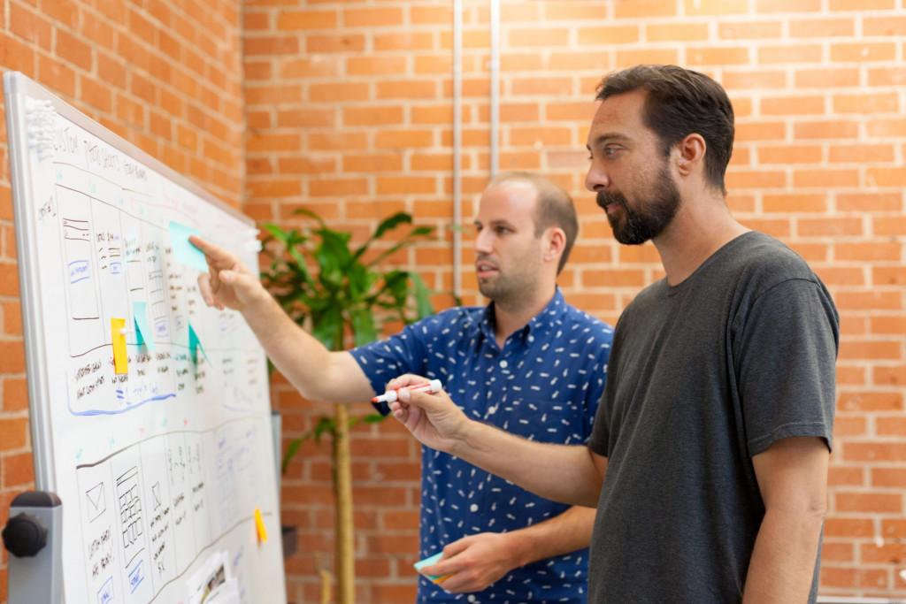 2 hommes travaillent sur le marketing automation sur un tableau blanc