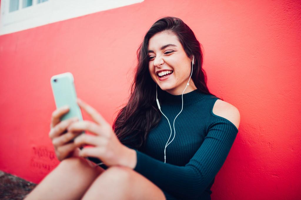 Femme rigole devant son smartphone