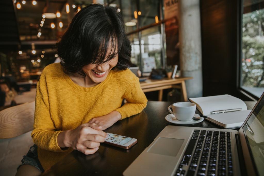 Femme sourie devant son mobile dans un café
